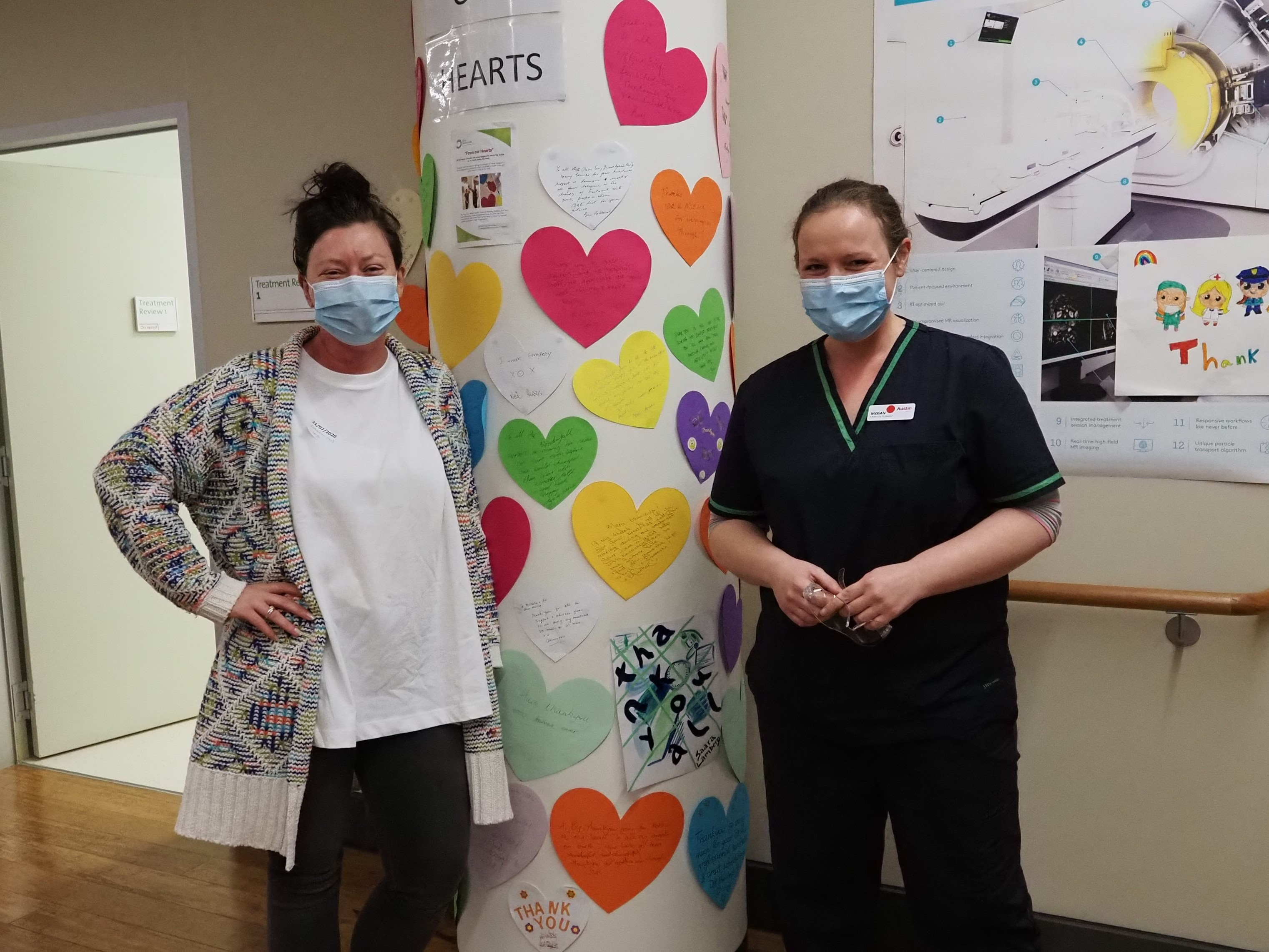 Nardia with Radiation Therapist Megan Hall in front of thank-you messages to hospital staff