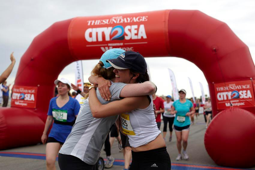 women hugging at finish line